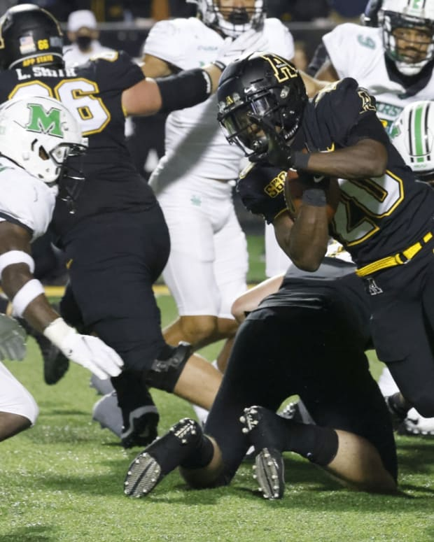 Sep 23, 2021; Boone, North Carolina, USA; Appalachian State Mountaineers running back Nate Noel (20) runs the ball past Marshall Thundering Herd defensive lineman Shane Simmons (34) as safety Nazeeh Johnson (13) looks to make the stoop during the second half at Kidd Brewer Stadium. Mandatory Credit: Reinhold Matay-USA TODAY Sports