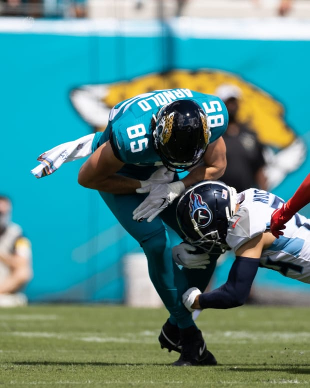 Jacksonville, Florida, USA; Jacksonville Jaguars tight end Dan Arnold (85) loses the ball after a hit from Tennessee Titans cornerback Elijah Molden (24) during the first quarter at TIAA Bank Field.