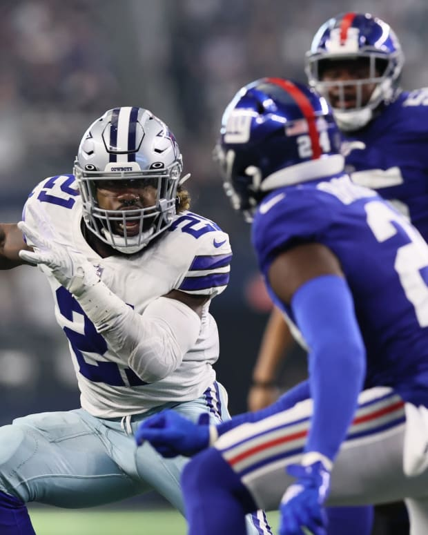 Oct 10, 2021; Arlington, Texas, USA; Dallas Cowboys running back Ezekiel Elliott (21) carries teh ball as New York Giants cornerback James Bradberry (24) defends in the third quarter at AT&T Stadium.
