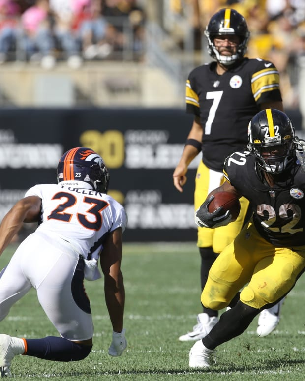 Pittsburgh Steelers running back Najee Harris (22) runs the ball Denver Broncos cornerback Kyle Fuller (23) during the third quarter against at Heinz Field. The Steelers won 27-19.