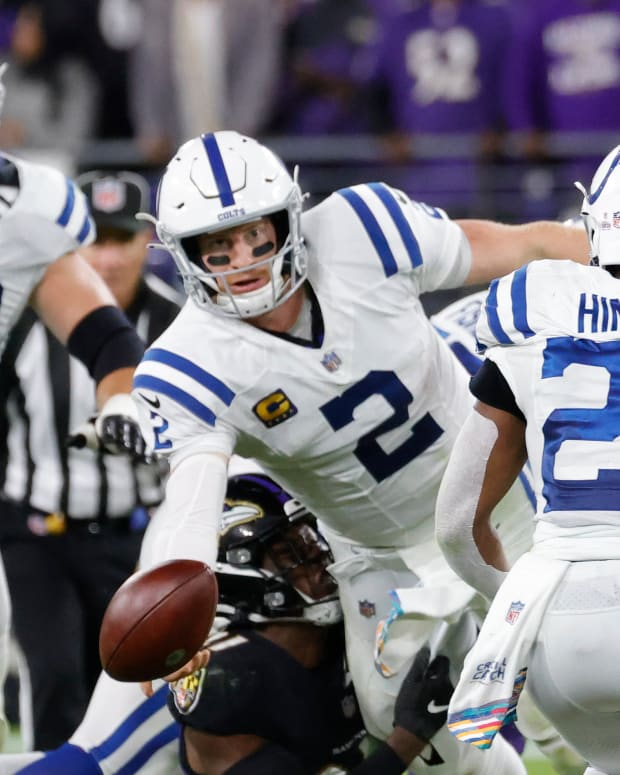 Oct 11, 2021; Baltimore, Maryland, USA; Indianapolis Colts quarterback Carson Wentz (2) attempts a shovel pass to Colts running back Nyheim Hines (21) against the Baltimore Ravens during the fourth quarter at M&T Bank Stadium.