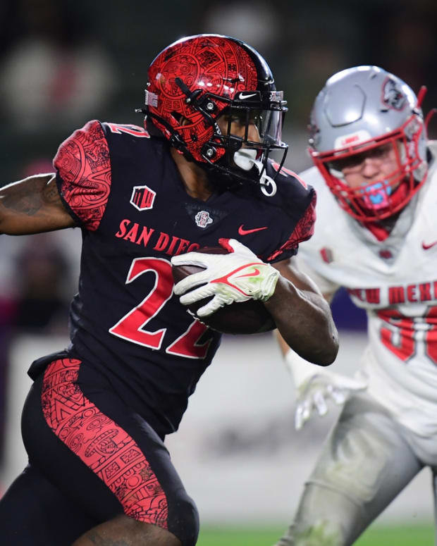 Oct 9, 2021; Carson, California, USA; San Diego State Aztecs running back Greg Bell (22) runs the ball against New Mexico Lobos defensive end Joey Noble (98) during the second half at Dignity Health Sports Park. Mandatory Credit: Gary A. Vasquez-USA TODAY Sports