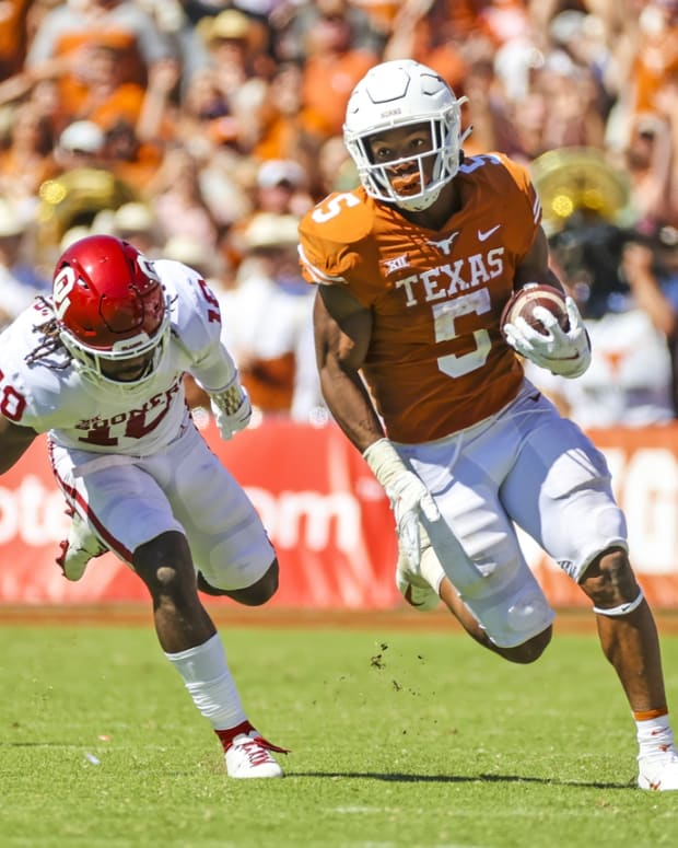 Oct 9, 2021; Dallas, Texas, USA; Texas Longhorns running back Bijan Robinson (5) runs with the ball as Oklahoma Sooners safety Pat Fields (10) defends during the game at the Cotton Bowl. Mandatory Credit: Kevin Jairaj-USA TODAY Sports