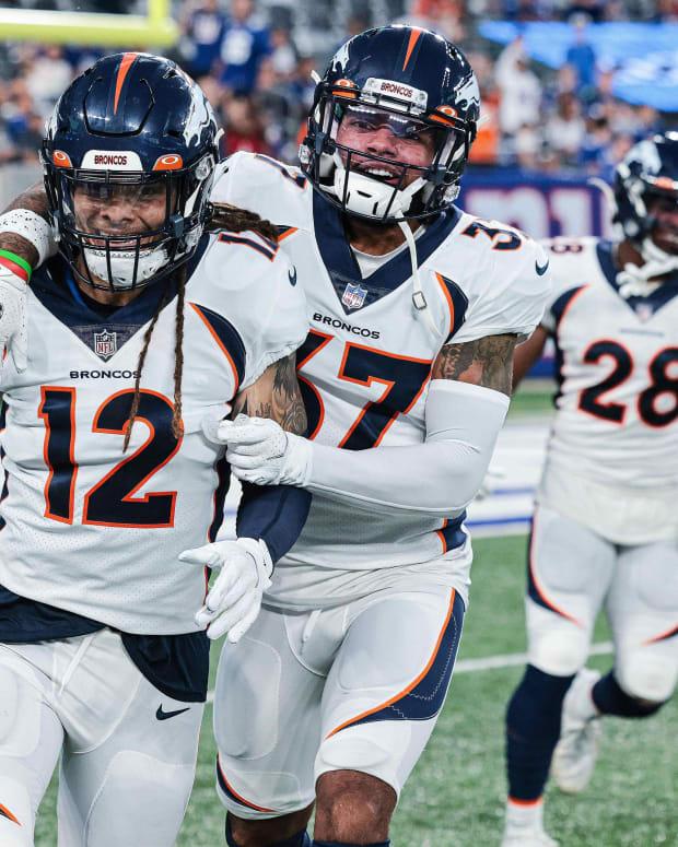 Denver Broncos defensive back Mike Ford (12) celebrates a tackle on a punt return with defensive back P.J. Locke (37) during the second half against the New York Giants at MetLife Stadium.