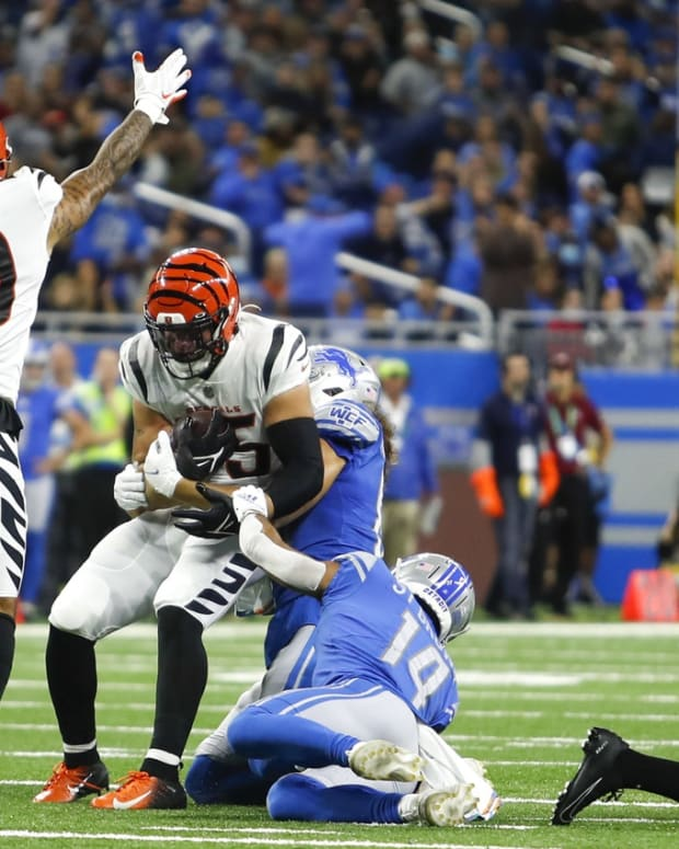 Oct 17, 2021; Detroit, Michigan, USA; Cincinnati Bengals linebacker Logan Wilson (55) gets the turnover from Detroit Lions wide receiver Amon-Ra St. Brown (14) as free safety Jessie Bates (30) signals Bengals ball during the first quarter at Ford Field. Mandatory Credit: Raj Mehta-USA TODAY Sports