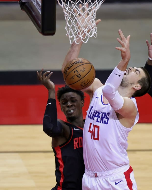 Apr 23, 2021; Houston, Texas, USA; Ivica Zubac #40 of the LA Clippers loses control of the ball as he shoots between John Wall #1 and Jae'Sean Tate #8 of the Houston Rockets during the first quarter at Toyota Center. Mandatory Credit: Carmen Mandato/POOL PHOTOS-USA TODAY Sports