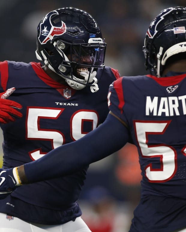 Aug 21, 2021; Arlington, Texas, USA; Houston Texans outside linebacker Whitney Mercilus (59) and linebacker Jake Martin (54) celebrate a turnover in the first quarter against the Dallas Cowboys at AT&T Stadium. Mandatory Credit: Tim Heitman-USA TODAY Sports
