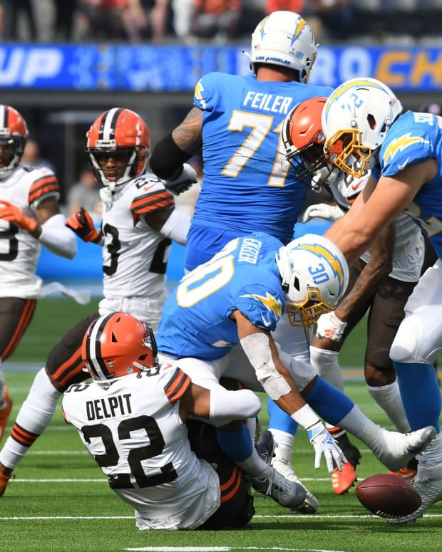 Oct 10, 2021; Inglewood, California, USA; Los Angeles Chargers running back Austin Ekeler (30) fumbles the ball after being tackled by Cleveland Browns defensive back Grant Delpit (22) in the first half at SoFi Stadium. Mandatory Credit: Richard Mackson-USA TODAY Sports