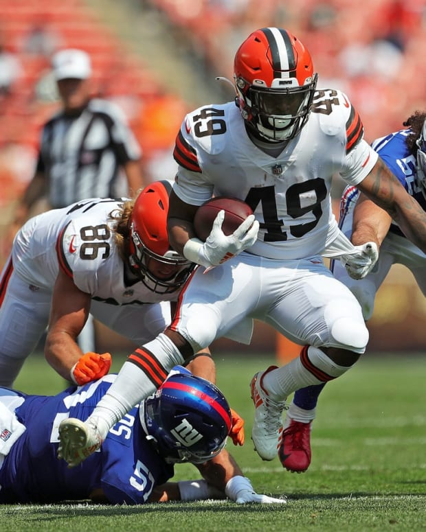 Cleveland Browns running back John Kelly (49) breaks away from New York Giants defensive end Niko Lalos (57) and New York Giants linebacker Devante Downs (52) as he rushes for a first down during the second half of an NFL preseason football game, Sunday, Aug. 22, 2021, in Cleveland, Ohio. [Jeff Lange/Beacon Journal] Brownsgiants 6