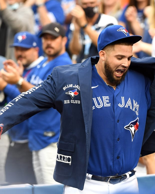 Oct 2, 2021; Toronto, Ontario, CAN; Toronto Blue Jays pitcher Alek Manoah (6) is helped into the team home run jacket by manager Charlie Montoyo (25) at the end of the seventh inning at Rogers Centre.
