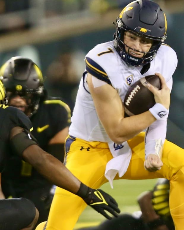 Chase Garbers tries to elude an Oregon tackler
