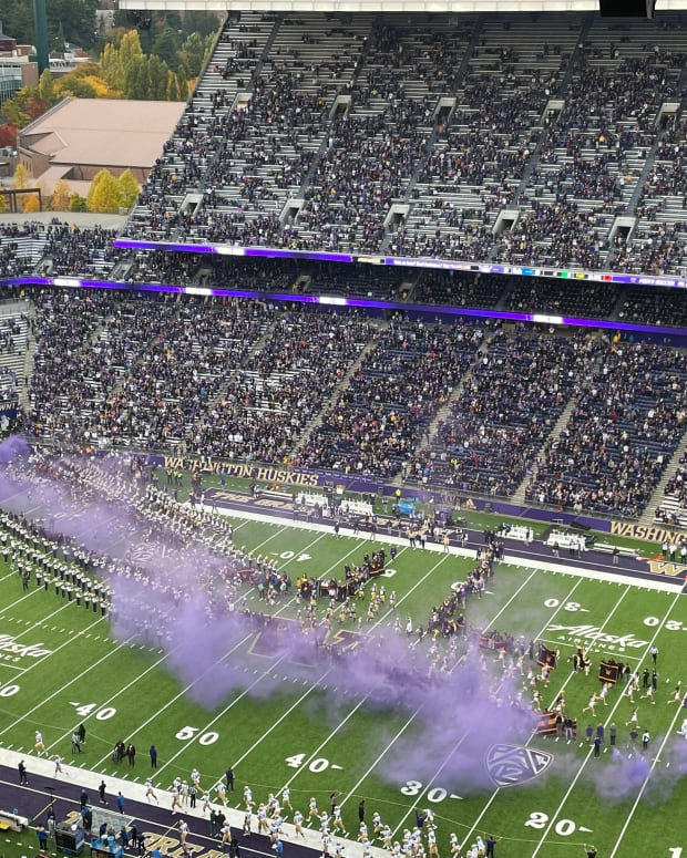 Purple smoke greets the UW football team as it enters the field.