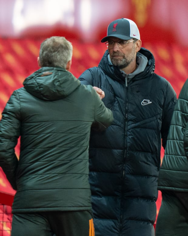 Liverpool's manager Jurgen Klopp (C) fist bumps Manchester United's manager Ole Gunnar Solskjaer (L) after the Premier League match between Manchester United and Liverpool at Old Trafford in Manchester, Britain, on May 13, 2021.