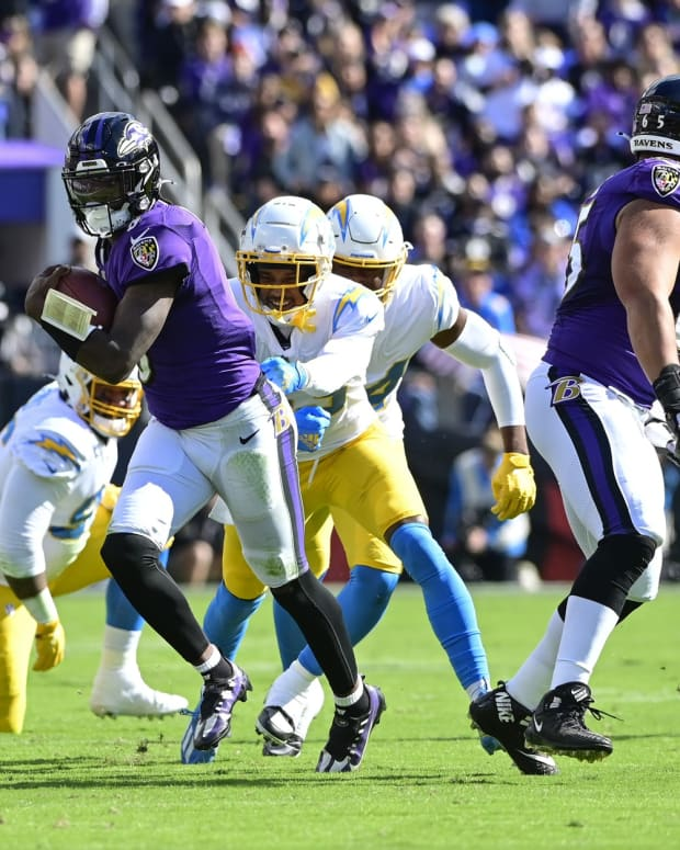 Oct 17, 2021; Baltimore, Maryland, USA; Baltimore Ravens quarterback Lamar Jackson (8) runs through Los Angeles Chargers defenders during the first half at M&T Bank Stadium. Mandatory Credit: Tommy Gilligan-USA TODAY Sports