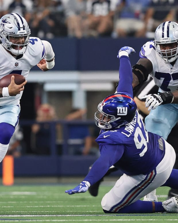 Oct 10, 2021; Arlington, Texas, USA; Dallas Cowboys quarterback Dak Prescott (4) runs with the ball pas New York Giants defensive tackle Dexter Lawrence (97) in the first quarter at AT&T Stadium.