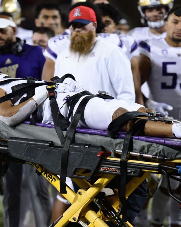 An injured Alex Cook leaves on a stretcher, something that UW teammate MJ Tafisi experienced in the same stadium in 2019.