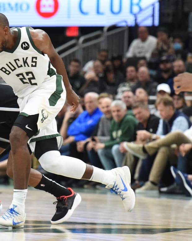 Oct 19, 2021; Milwaukee, Wisconsin, USA; Milwaukee Bucks forward Khris Middleton (22) and Brooklyn Nets guard Patty Mills (8) battle for possession of the ball in the second half at Fiserv Forum. Mandatory Credit: Michael McLoone-USA TODAY Sports
