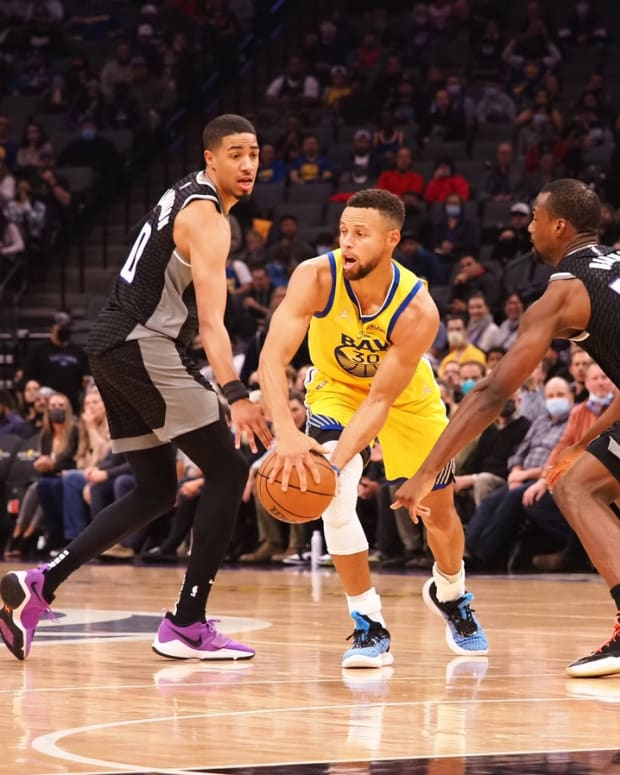 Oct 24, 2021; Sacramento, California, USA; Golden State Warriors guard Stephen Curry (30) passes the ball between Sacramento Kings guard Tyrese Haliburton (0) and forward Harrison Barnes (40) during the first quarter at Golden 1 Center. Mandatory Credit: Kelley L Cox-USA TODAY Sports