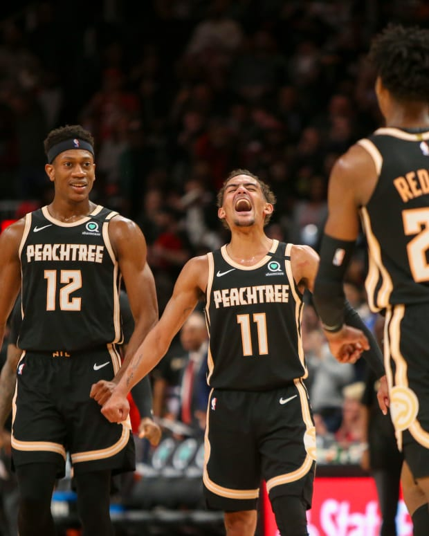 Atlanta Hawks guard Trae Young (11) celebrates with forward De'Andre Hunter (12) and guard Kevin Huerter (3) after a basket by guard Cam Reddish (22) against the Miami Heat in the second half at State Farm Arena.