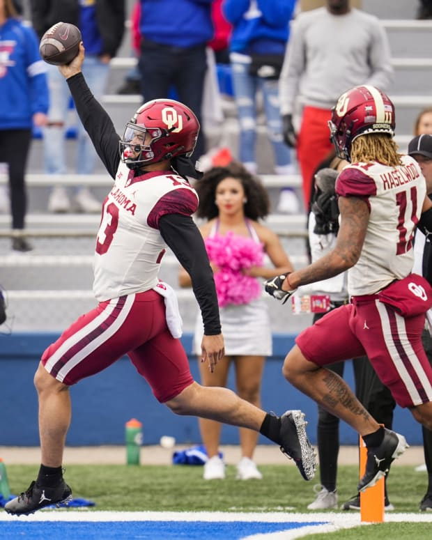 Oct 23, 2021; Lawrence, Kansas, USA; Oklahoma Sooners quarterback Caleb Williams (13) scores a touchdown as wide receiver Jadon Haselwood (11) looks on during the second half against the Kansas Jayhawks at David Booth Kansas Memorial Stadium.
