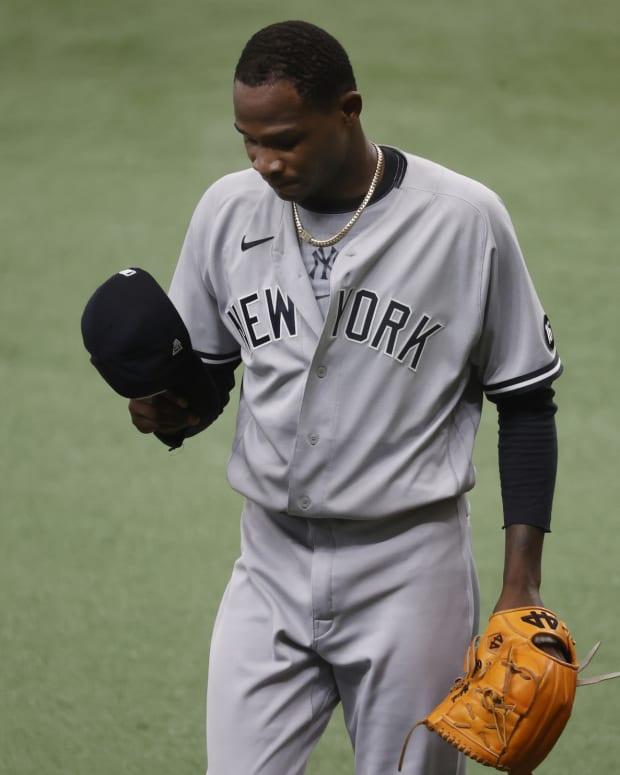 Yankees SP Domingo Germán looking in hat