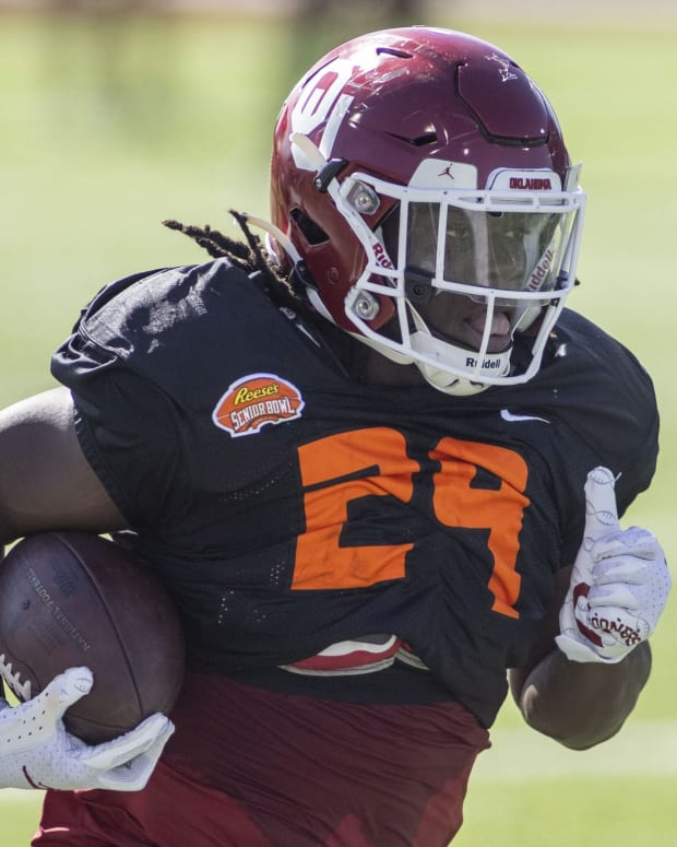 Jan 28, 2021; Mobile, Alabama, USA; National running back Rhamondre Stevenson of Oklahoma (29) runs the ball during National practice at Hancock Whitney Stadium.
