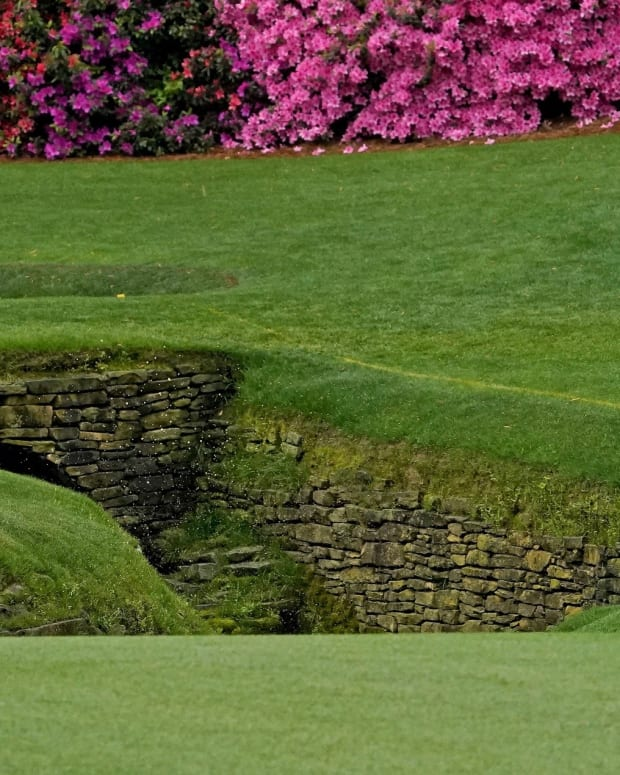 Collin Morikawa hits out of a deep bunker at Augusta National
