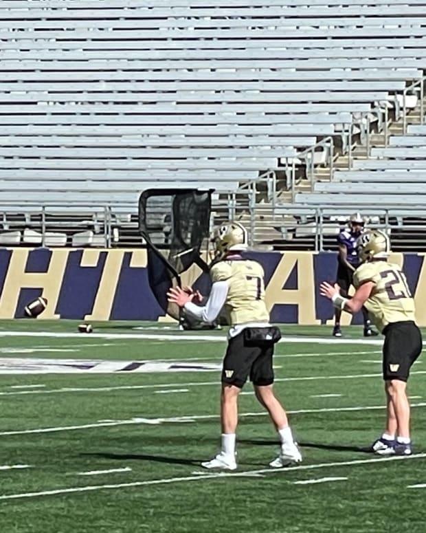 The Husky quarterbacks run through a Saturday drill as John Donovan looks on.