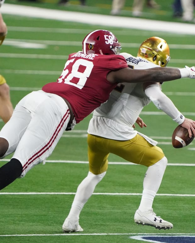 Alabama Crimson Tide defensive lineman Christian Barmore (58) sacks Notre Dame Fighting Irish quarterback Ian Book (12) in the third quarter during the Rose Bowl at AT&T Stadium.