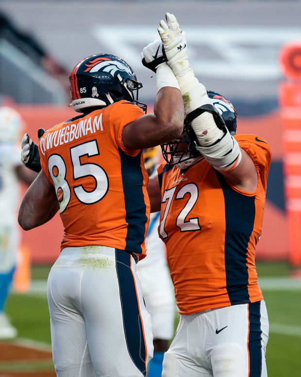 Denver Broncos tight end Albert Okwuegbunam (85) celebrates his touchdown with offensive tackle Garett Bolles (72) in the fourth quarter against the Los Angeles Chargers at Empower Field at Mile High.