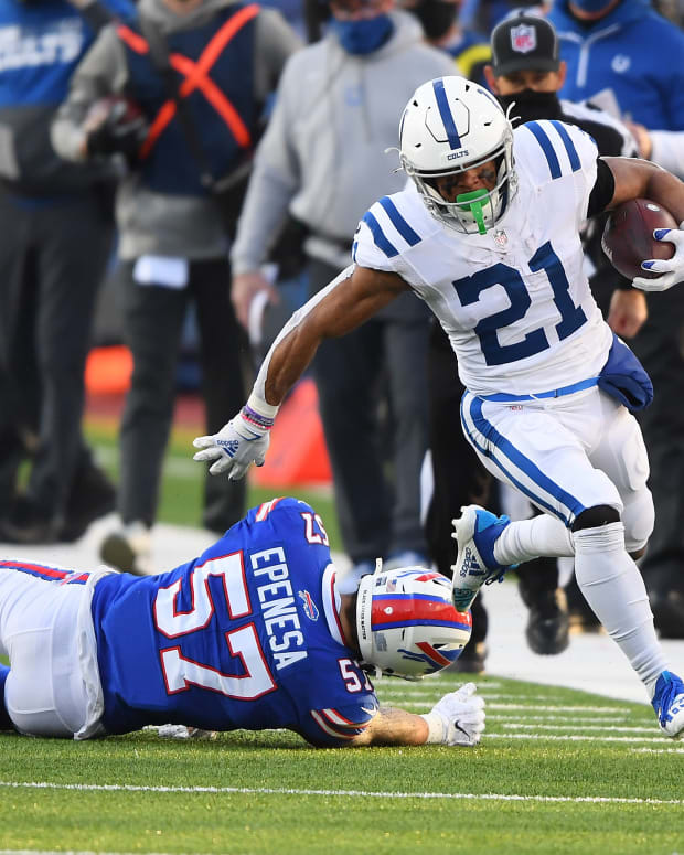 Jan 9, 2021; Orchard Park, New York, USA; Indianapolis Colts running back Nyheim Hines (21) runs the ball ahead of Buffalo Bills defensive end A.J. Epenesa (57) during the second half in the AFC Wild Card game at Bills Stadium. Mandatory Credit: Rich Barnes-USA TODAY Sports