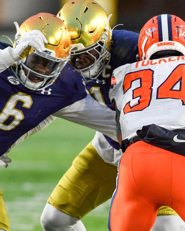 Dec 5, 2020; South Bend, Indiana, USA; Syracuse Orange running back Sean Tucker (34) is tackled by Notre Dame Fighting Irish linebacker Jeremiah Owusu-Koramoah (6) in the third quarter at Notre Dame Stadium. Mandatory Credit: Matt Cashore-USA TODAY Sports