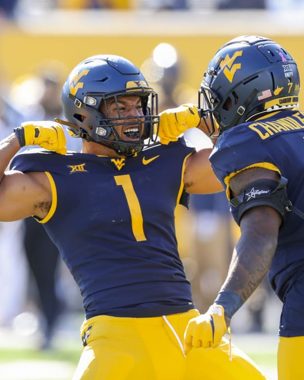 Oct 17, 2020; Morgantown, West Virginia, USA; West Virginia Mountaineers linebacker Tony Fields II (1) celebrates with linebacker Josh Chandler-Semedo (7) after a defensive stop during the third quarter against the Kansas Jayhawks at Mountaineer Field at Milan Puskar Stadium
