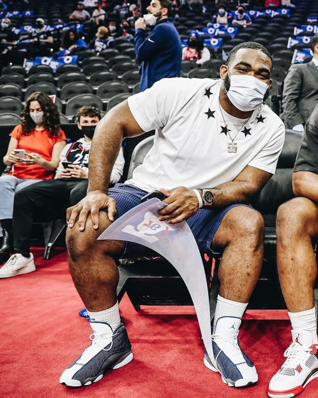 Brandon Graham (left), Jalen Hurts, and DeVonta Smith take in a Sixers game