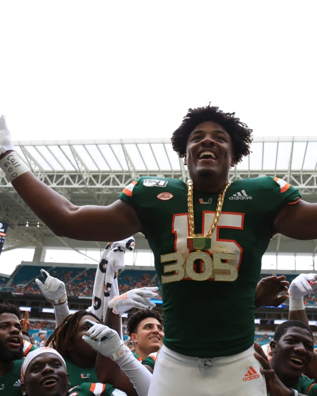 Miami Hurricanes defensive lineman Gregory Rousseau (15) celebrates wearing the turnover chain during the first quarter of a football game against the Central Michigan Chippewas at Hard Rock Stadium.