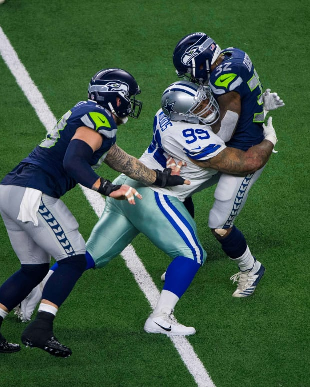 Jan 5, 2019; Arlington, TX, USA; Dallas Cowboys defensive tackle Antwaun Woods (99) and Seattle Seahawks running back Chris Carson (32) and center Justin Britt (68) in action during an NFC Wild Card playoff football game between the Cowboys and the Seahawks at AT&T Stadium. Mandatory Credit: Jerome Miron-USA TODAY Sports