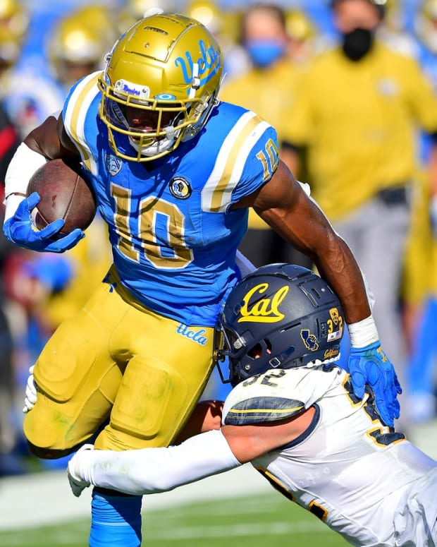 Nov 15, 2020; Pasadena, California, USA; UCLA Bruins running back Demetric Felton (10) runs for a first down against California Golden Bears safety Daniel Scott (32) in the first half at the Rose Bowl. Mandatory Credit: Jayne Kamin-Oncea-USA TODAY Sports
