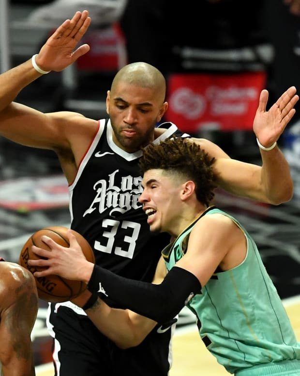 Mar 20, 2021; Los Angeles, California, USA; Charlotte Hornets guard LaMelo Ball (2) is fouled by Los Angeles Clippers guard Paul George (13) as Los Angeles Clippers forward Nicolas Batum (33) defends under the basket in the second half of the game at Staples Center. Mandatory Credit: Jayne Kamin-Oncea-USA TODAY Sports