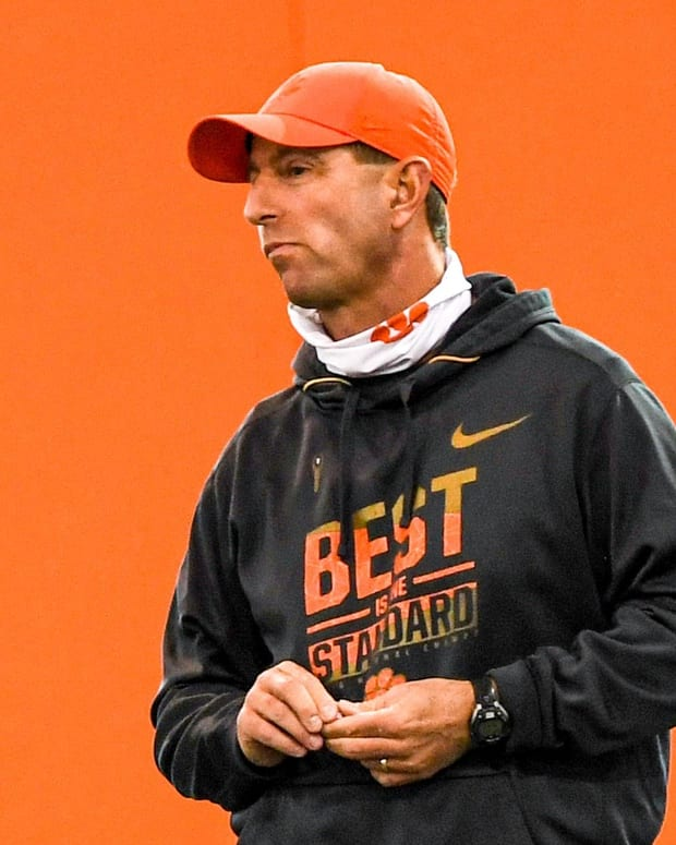 Clemson head coach Dabo Swinney watches players stretch during spring football practice in Clemson, S.C. Friday, March 5, 2021.