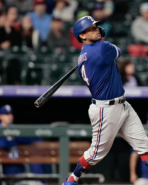Jun 1, 2021; Denver, Colorado, USA; Texas Rangers pinch hitter Khris Davis (4) watches his ball on a solo home run in the eighth inning against the Colorado Rockies at Coors Field.