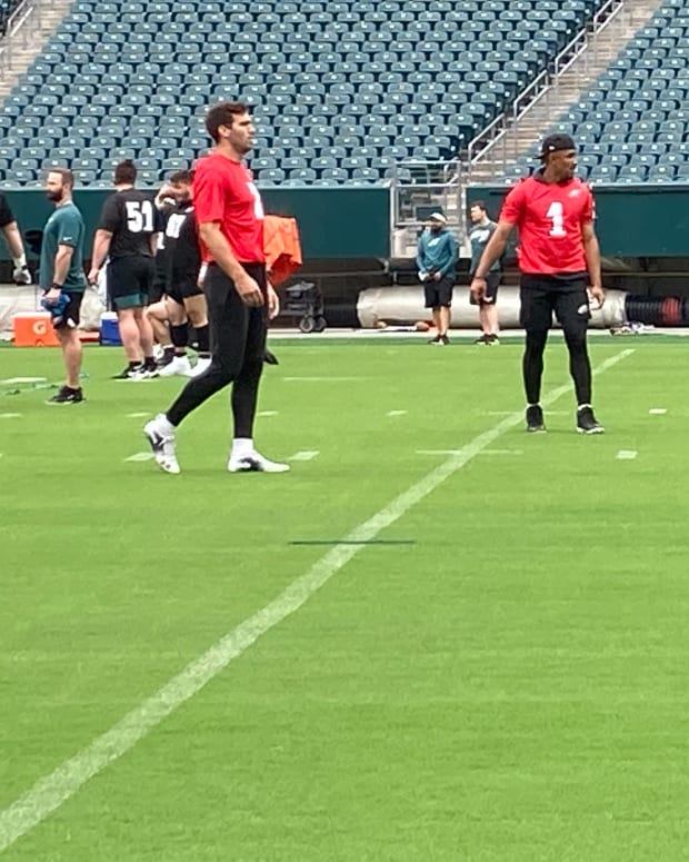 Eagles QBs Joe Flacco (left) and Jalen Hurts warm up prior to practice on June 4, 2021