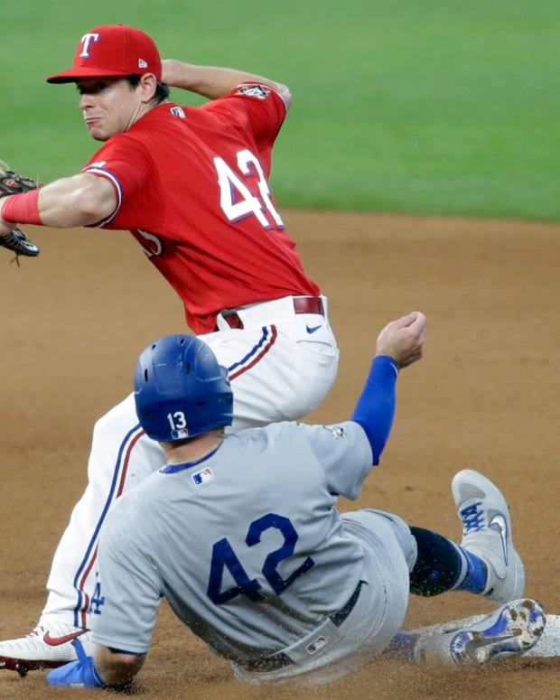 Aug 30, 2020; Arlington, Texas, USA; Texas Rangers second baseman Nick Solak (back) attempts to turn a double play on Los Angeles Dodgers third baseman Max Muncy (front) in the seventh inning at Globe Life Field.