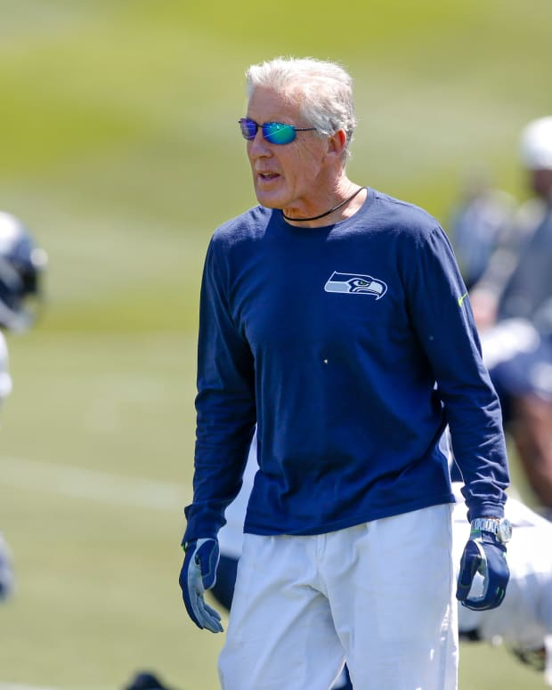 Seattle Seahawks head coach Pete Carroll watches warmups before a minicamp practice at the Virginia Mason Athletic Center.