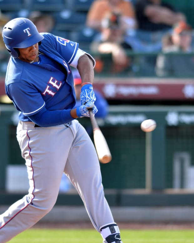 Mar 10, 2019; Scottsdale, AZ, USA; Texas Rangers infielder Curtis Terry (30) hits an RBI single during the ninth inning against the San Francisco Giants at Scottsdale Stadium.