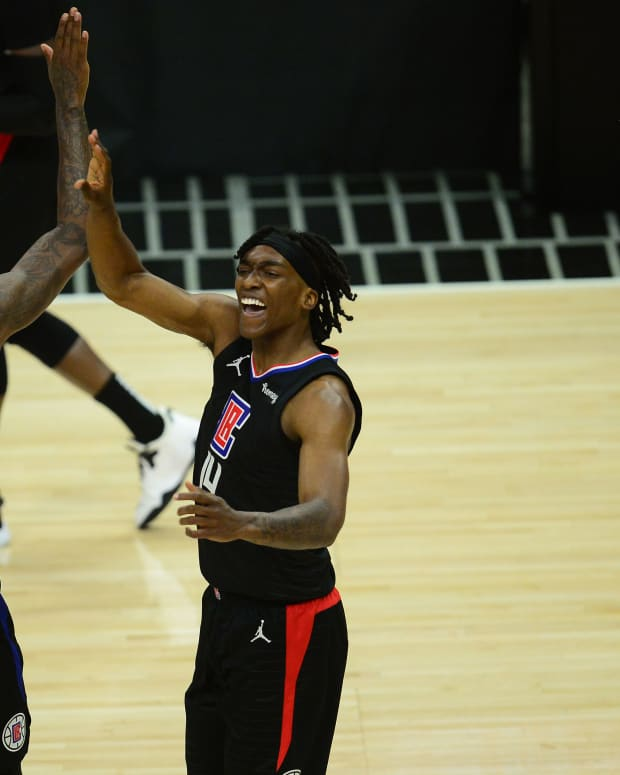 Jun 14, 2021; Los Angeles, California, USA; Los Angeles Clippers guard Terance Mann (14) reacts with guard Paul George (13) after scoring a basket and drawing a foul against the Utah Jazz during the first half in game four in the second round of the 2021 NBA Playoffs. at Staples Center. Mandatory Credit: Gary A. Vasquez-USA TODAY Sports