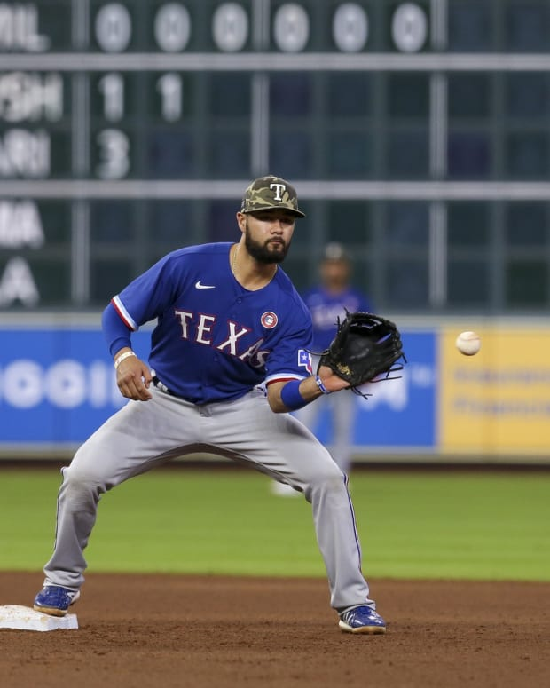 May 15, 2021; Houston, Texas, USA; Texas Rangers shortstop Isiah Kiner-Falefa (9) forces out Houston Astros shortstop Carlos Correa (1) at second base in the fifth inning at Minute Maid Park.