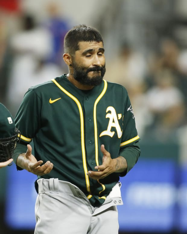 Jun 22, 2021; Arlington, Texas, USA; Oakland Athletics relief pitcher Sergio Romo (54) is checked for foreign substances by umpire Dan Iassogna (58)after the seventh inning against the Texas Rangers at Globe Life Field.
