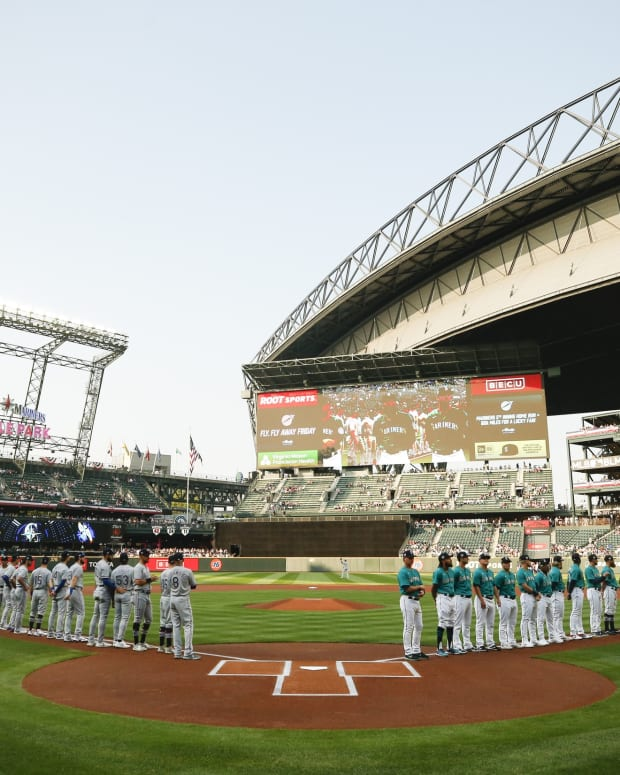 Jul 2, 2021; Seattle, Washington, USA; Texas Rangers, left, and Seattle Mariners, right, stand along the foul lines before a game at T-Mobile Park.