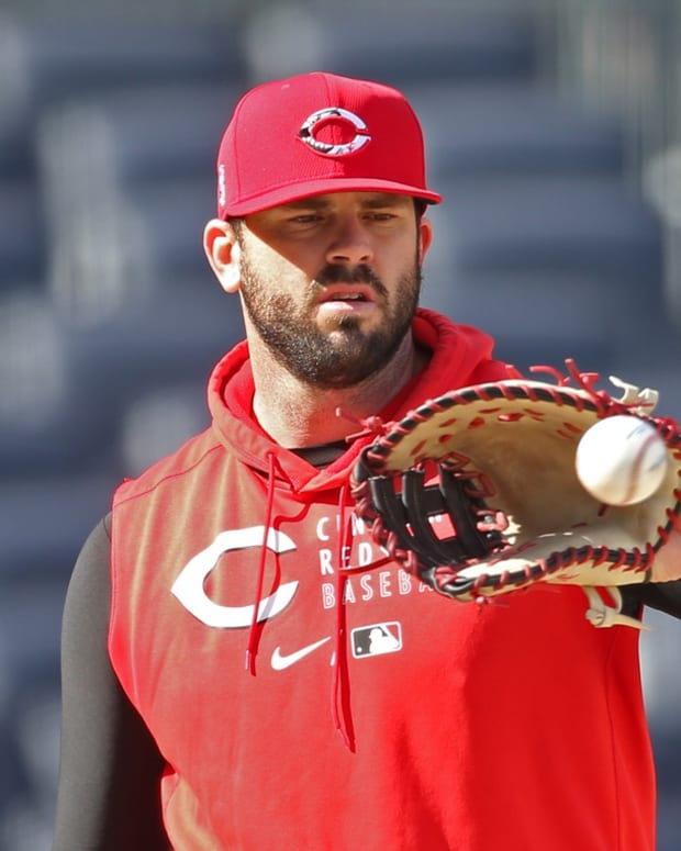 May 10, 2021; Pittsburgh, Pennsylvania, USA; Cincinnati Reds first baseman Mike Moustakas (9) plays catch on the field before the game against the Pittsburgh Pirates at PNC Park. Mandatory Credit: Charles LeClaire-USA TODAY Sports