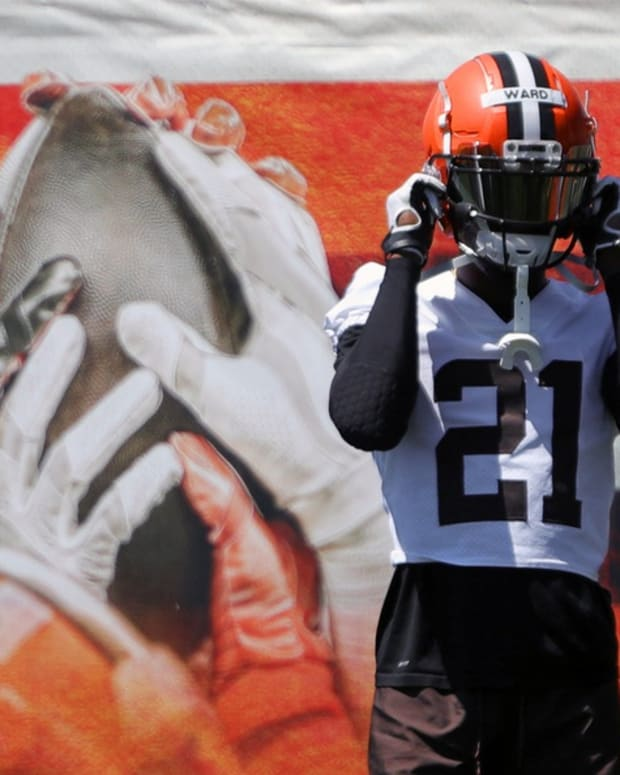 Cleveland Browns cornerback Denzel Ward (21) straps on his helmet as he takes the field during an NFL football practice at the team's training facility, Wednesday, June 16, 2021, in Berea, Ohio. Browns 11